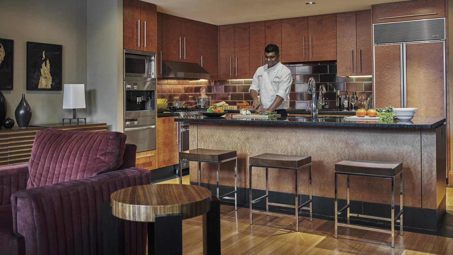 Chef prepares meal in kitchen that overlooks living room