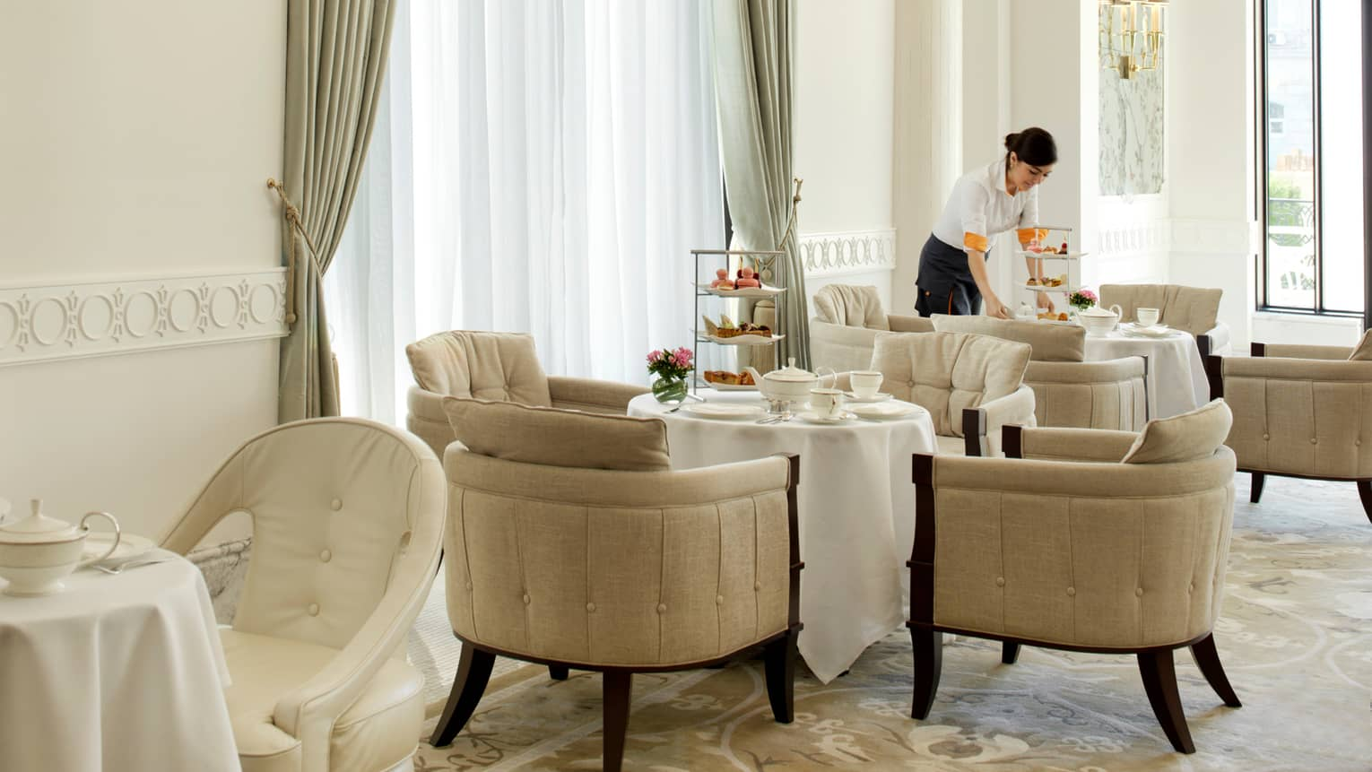 Server sets three-tiered trays with desserts and tea pots on round table in sunny Piazza dining room