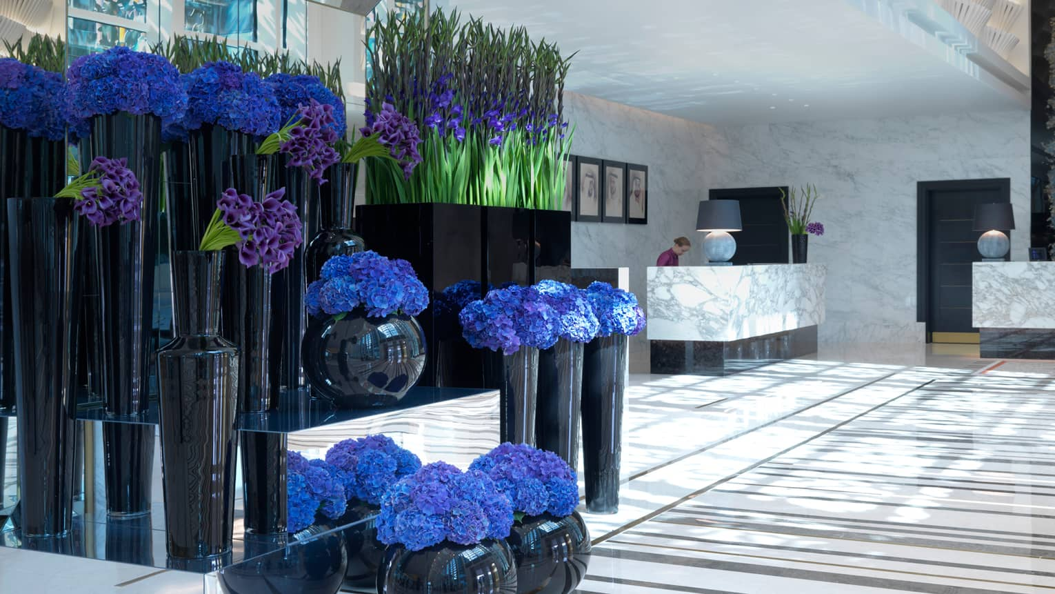 Tall black vases hold bouquets of purple and blue flowers in white marble hotel lobby