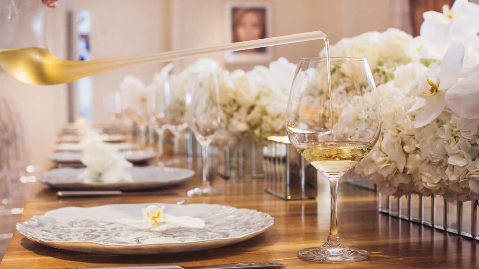 Close-up of glass of white wine, white roses along formal banquet table