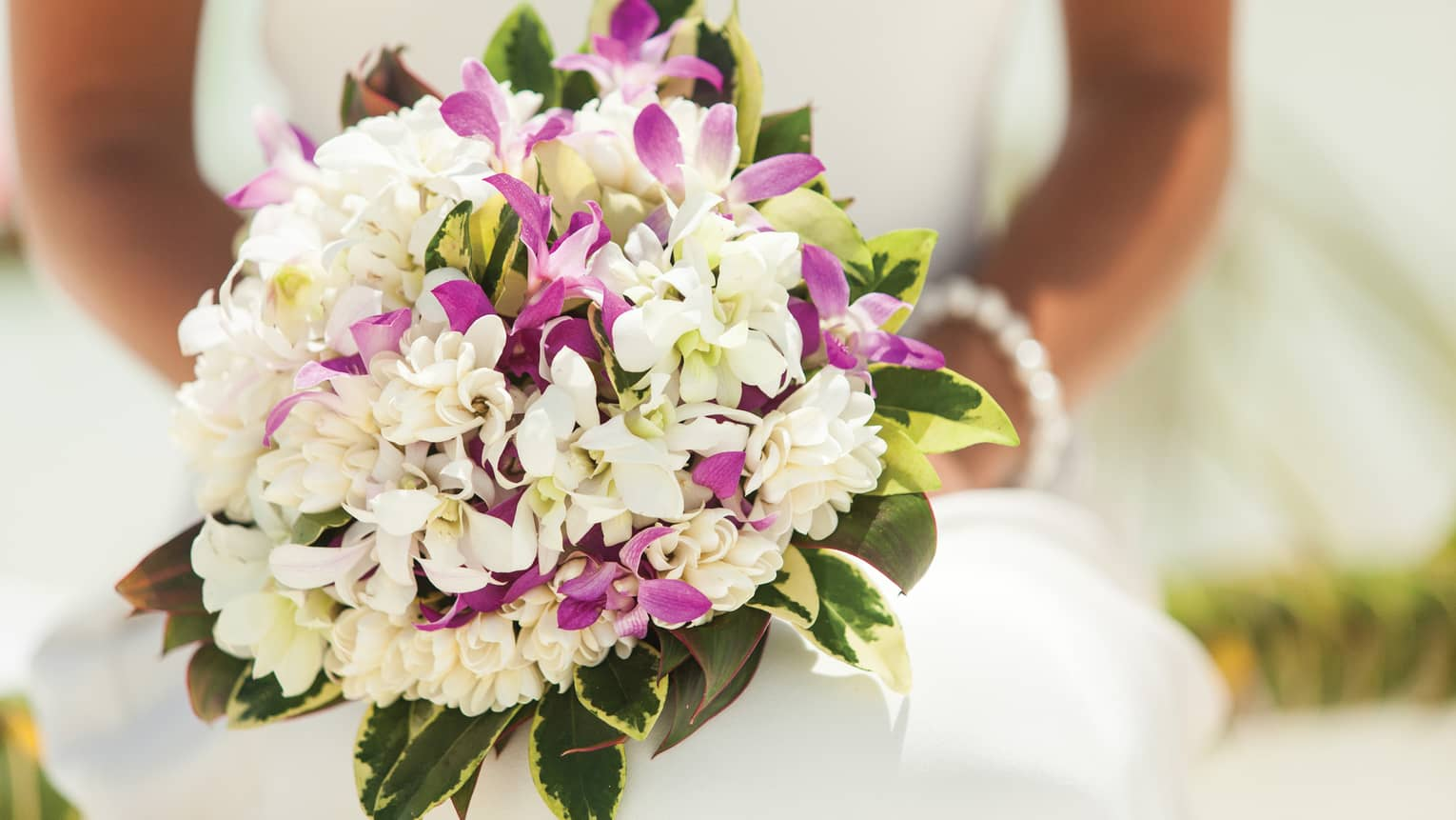 Close-up of bride holding wedding bouquet with purple and white flowers