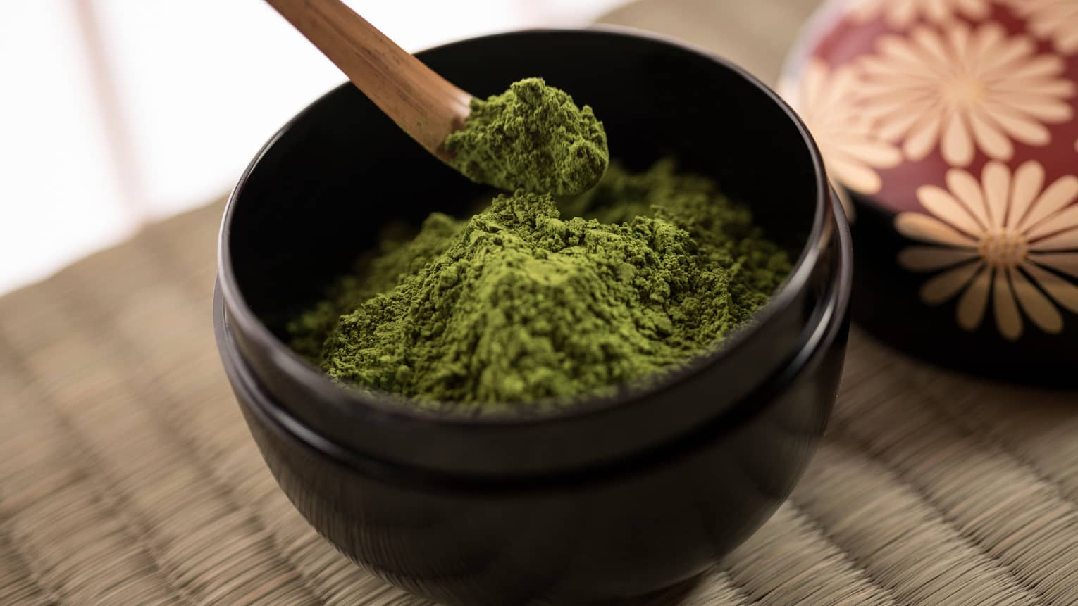 Close-up of green matcha tea powder in small black bowl, wood spoon