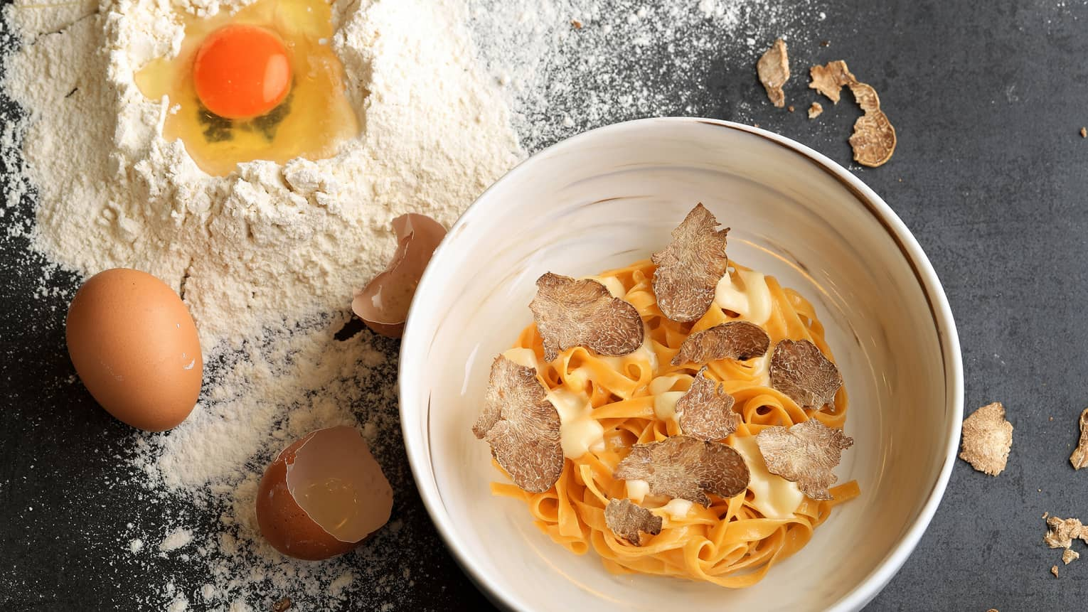 Aerial view of Truffle Spaghetti with mushroom garnish in bowl, cracked egg shells and powdered flour on counter