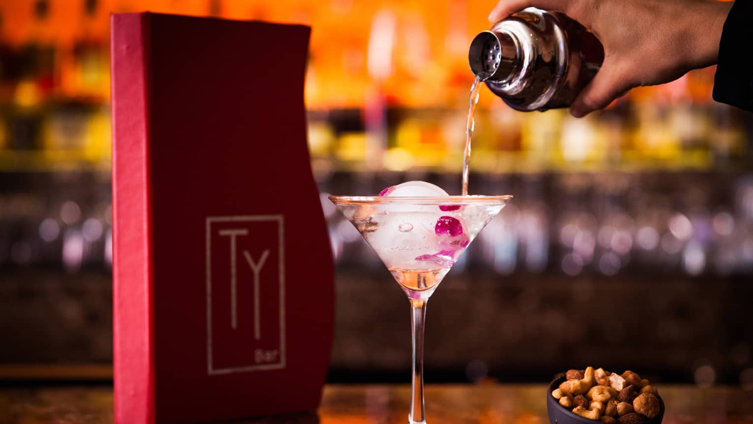 Red Ty Lounge menu on bar, bartender pours liquor into tall martini glass