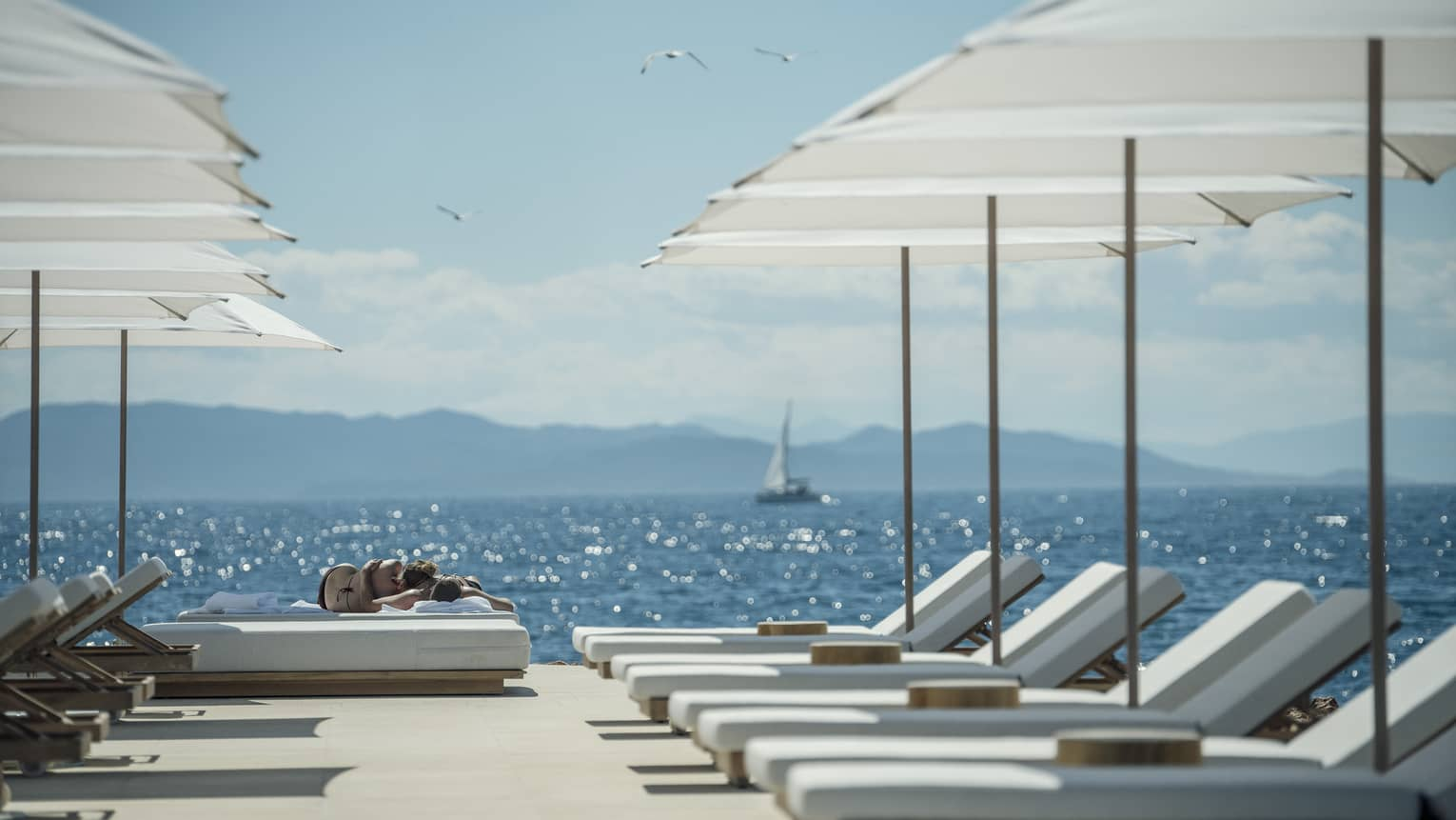 A sail boat sails in the distance while white lounge chairs are ready for guests and lined up next to the oceanside Nafsika Pool in Athens.