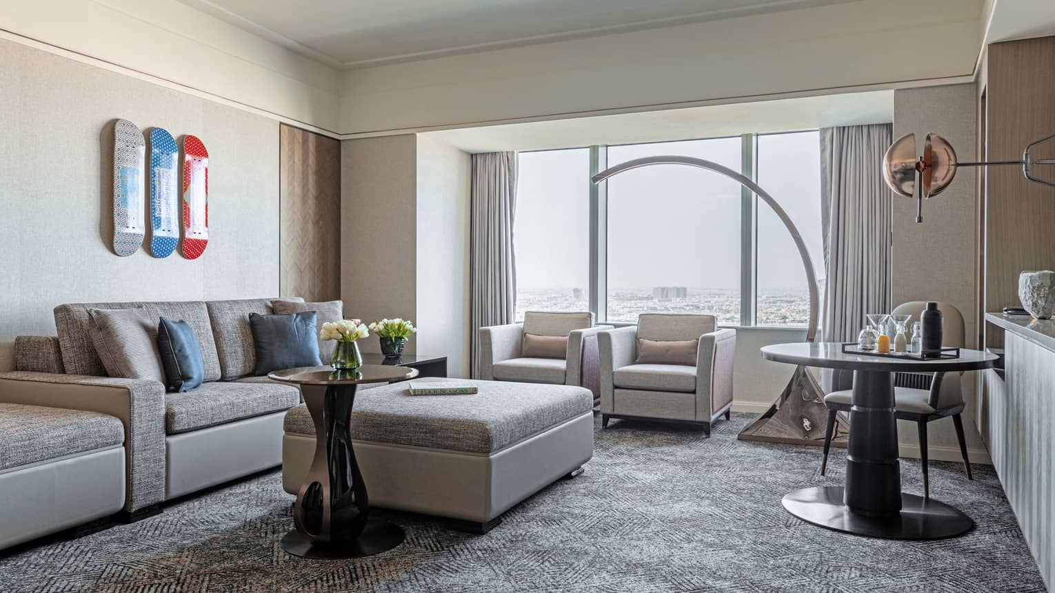 Living room with grey carpet, light grey sofa and ottoman, large curved floor lamp, windows