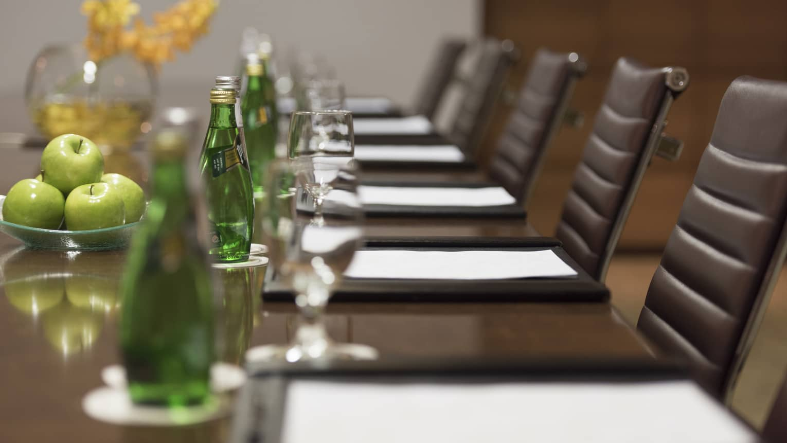 Close-up of business meeting table row of chairs, paper agendas, green glass bottles, apples