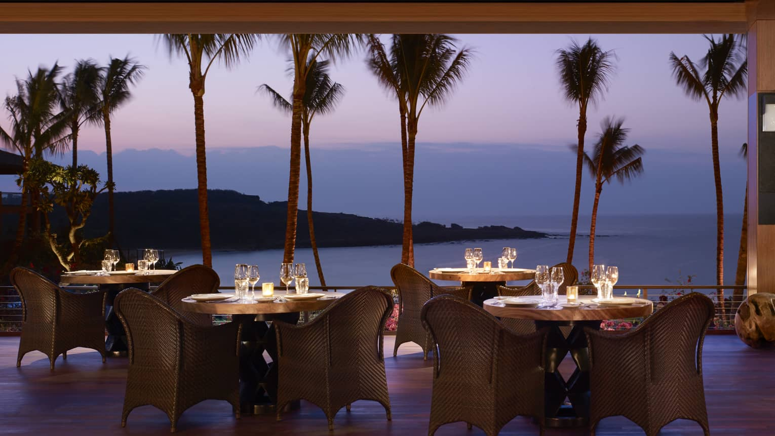 Wicker dining chairs around patio tables overlooking beach on One Forty patio at night