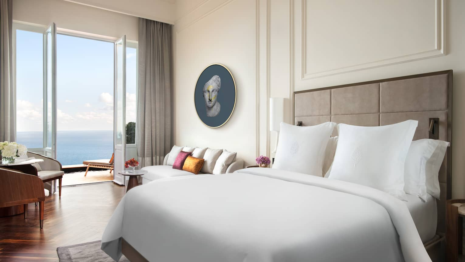 Hotel room with white king bed, white walls with crown molding, wood floors, walk-out sea-view balcony