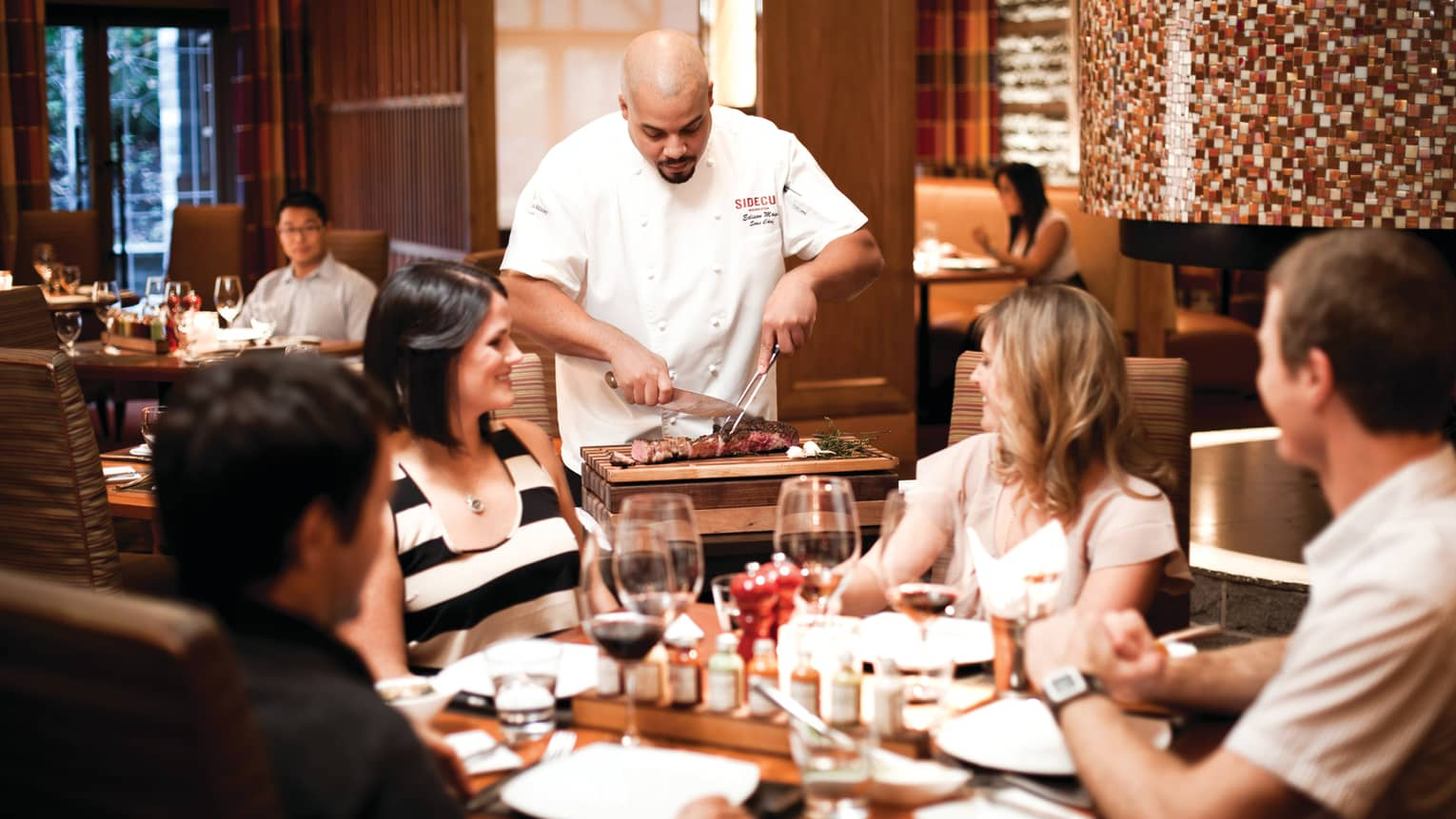 Chef slices steak on butcher board at dining table as guests watch, smile