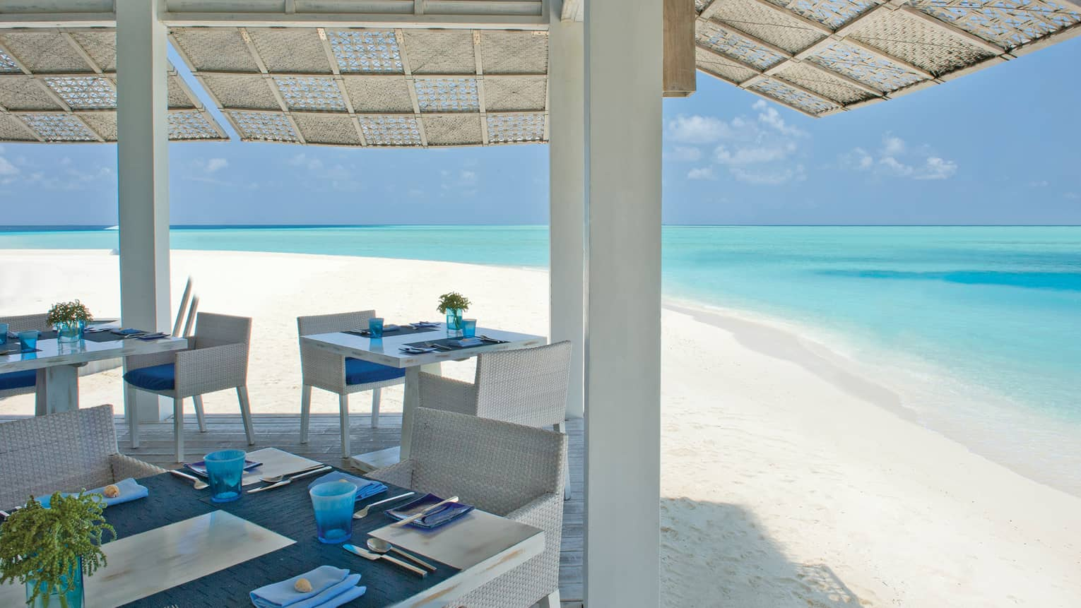 Dining tables, white wicker chairs on pavilion under woven roof by white sand beach, ocean