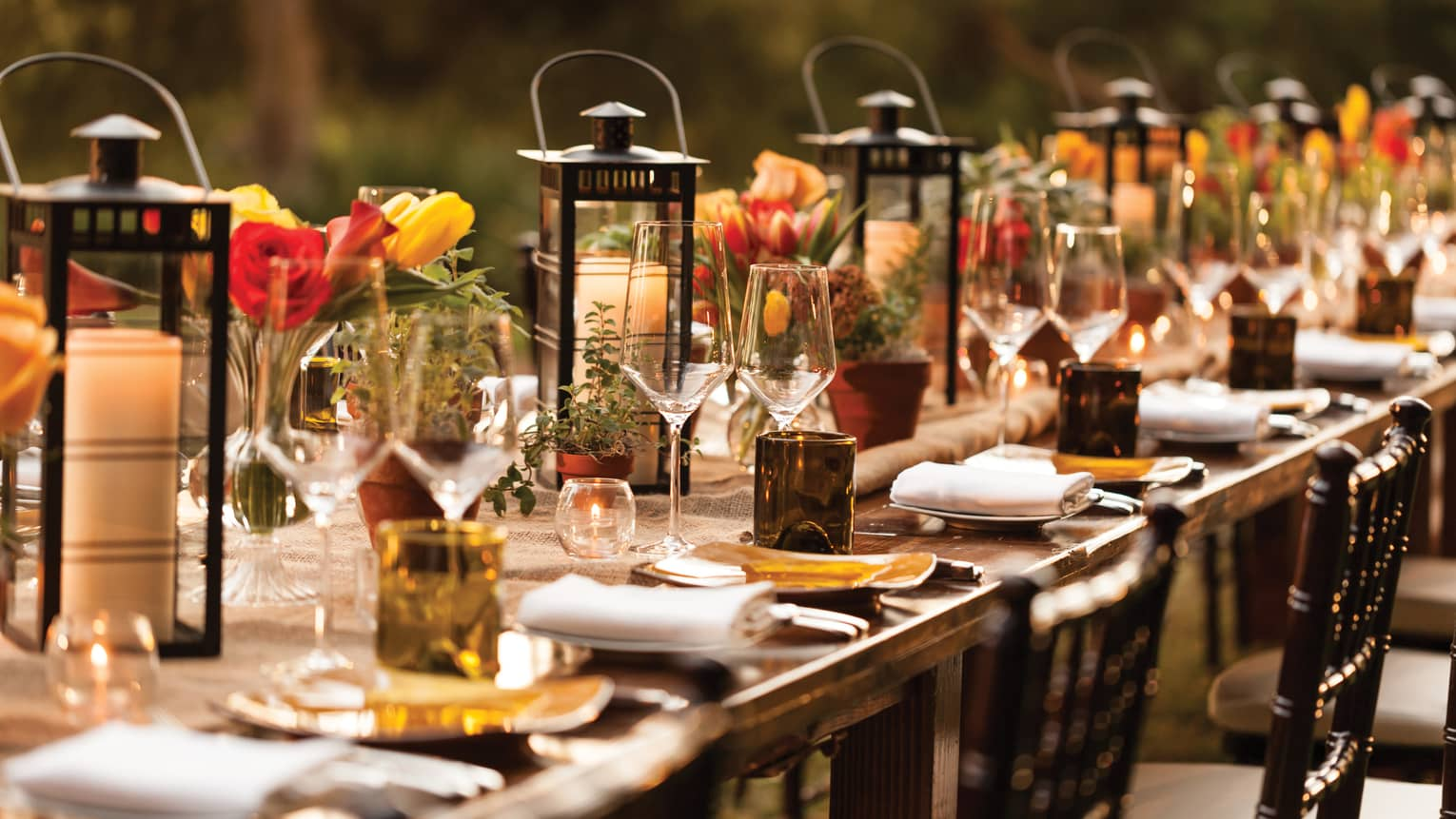 Close-up of long outdoor dining table set with lanterns, candles, wine glasses, flowers