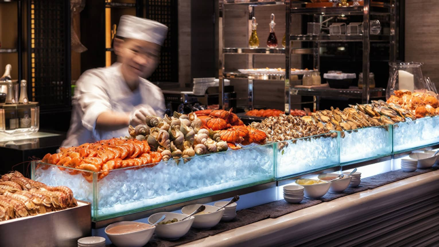 Chef reaches for snails on fresh seafood display on ice at bar