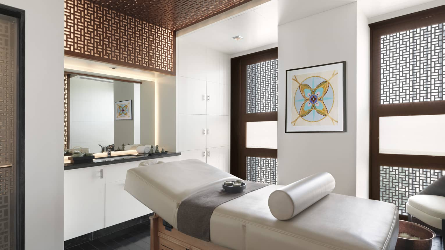 Spa massage table with rolled white leather pillow in front of vanity with sink, two windows