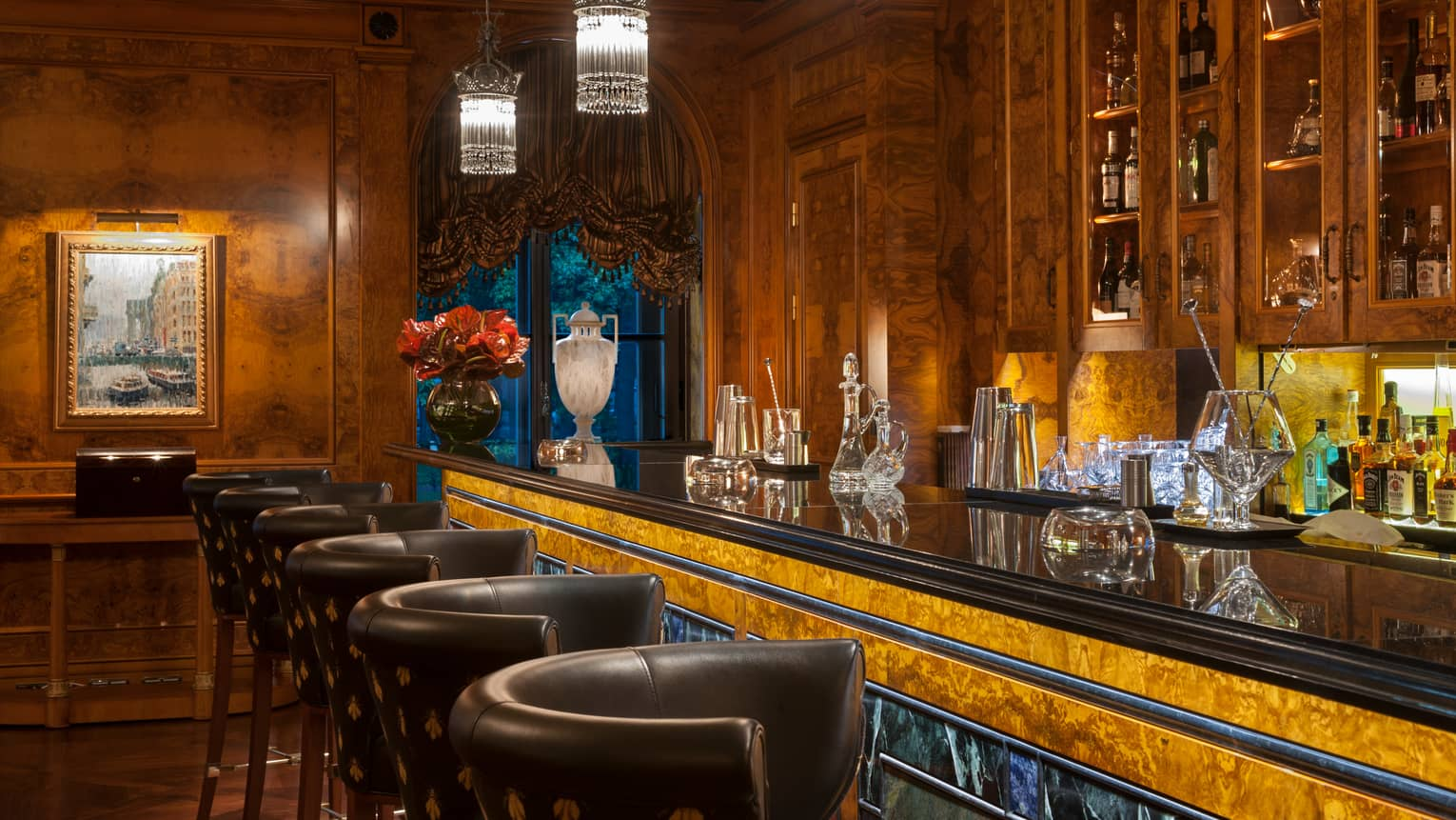 Xander lounge, long wood-grain bar lined with leather stools, crystal lights, jars