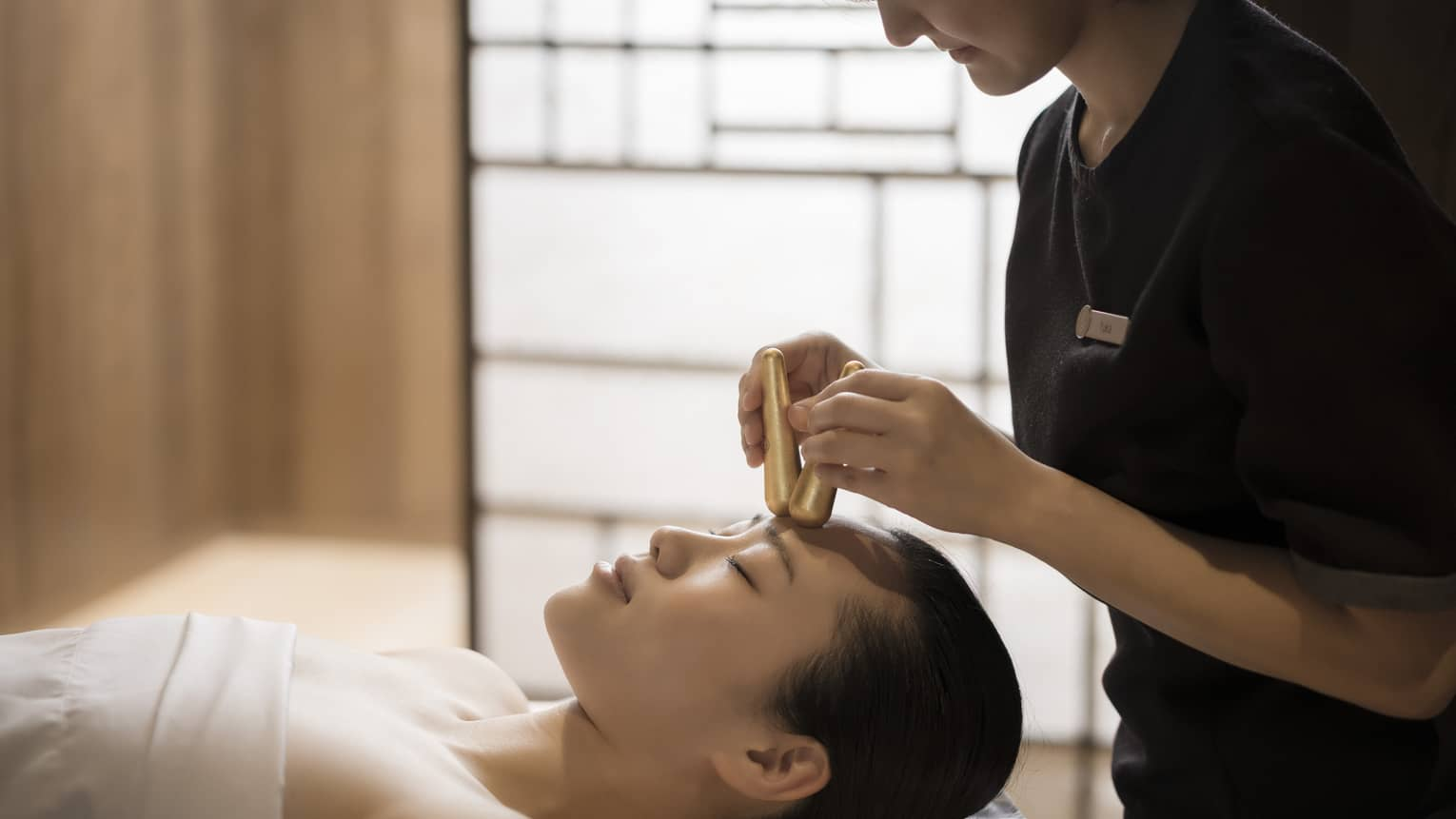 Close-up of massage therapist pressing gold acupressure batons on woman's forehead
