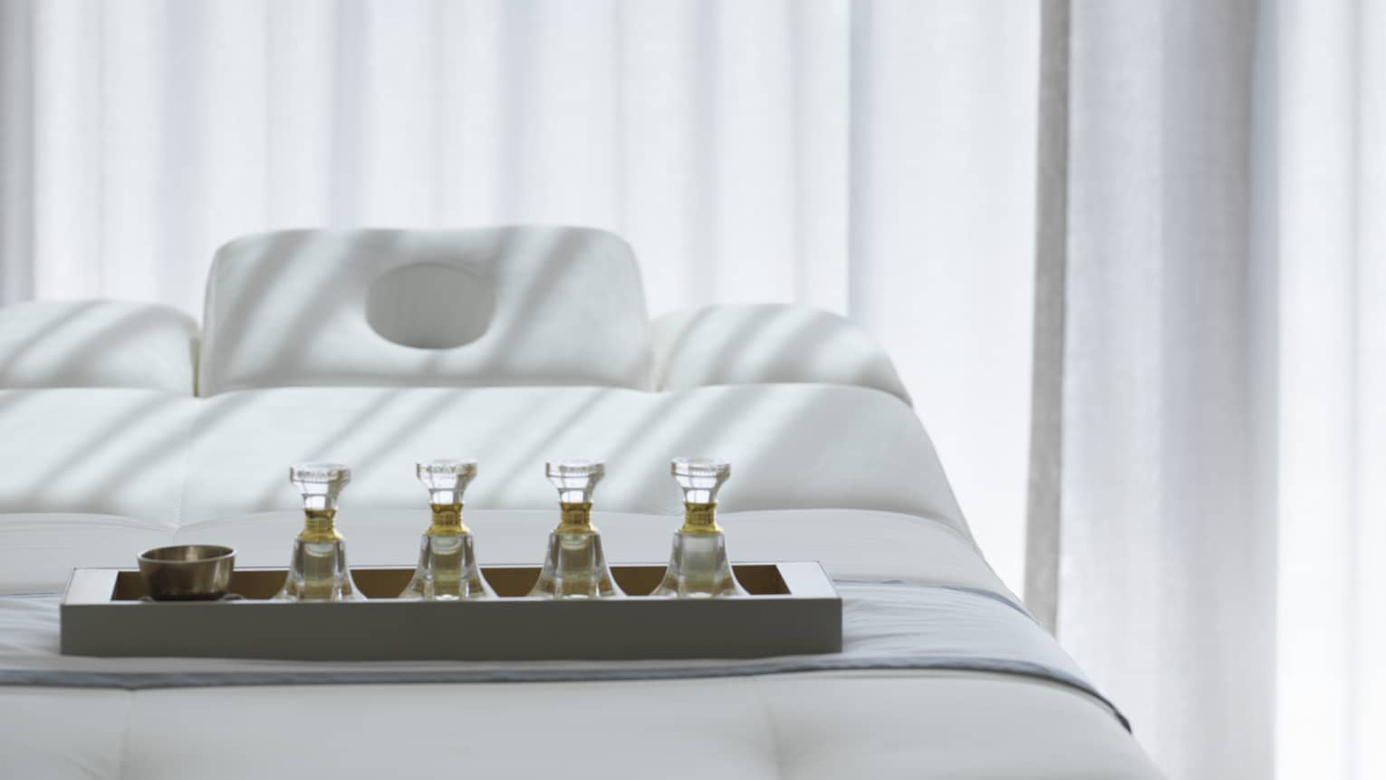 Tray with spa oils on massage treatment bed by white curtains