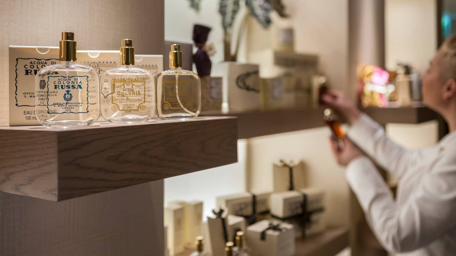 Close-up of three glass cologne bottles with out-of-focus person in background looking at retail store shelf
