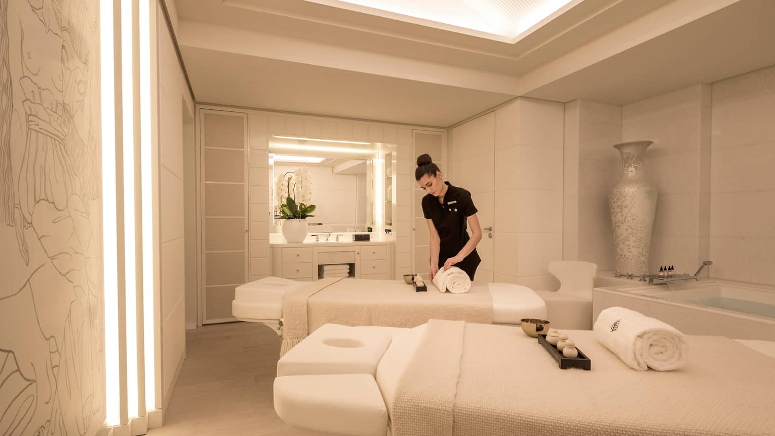 Spa staff rolls white towel on couples massage beds in white treatment room