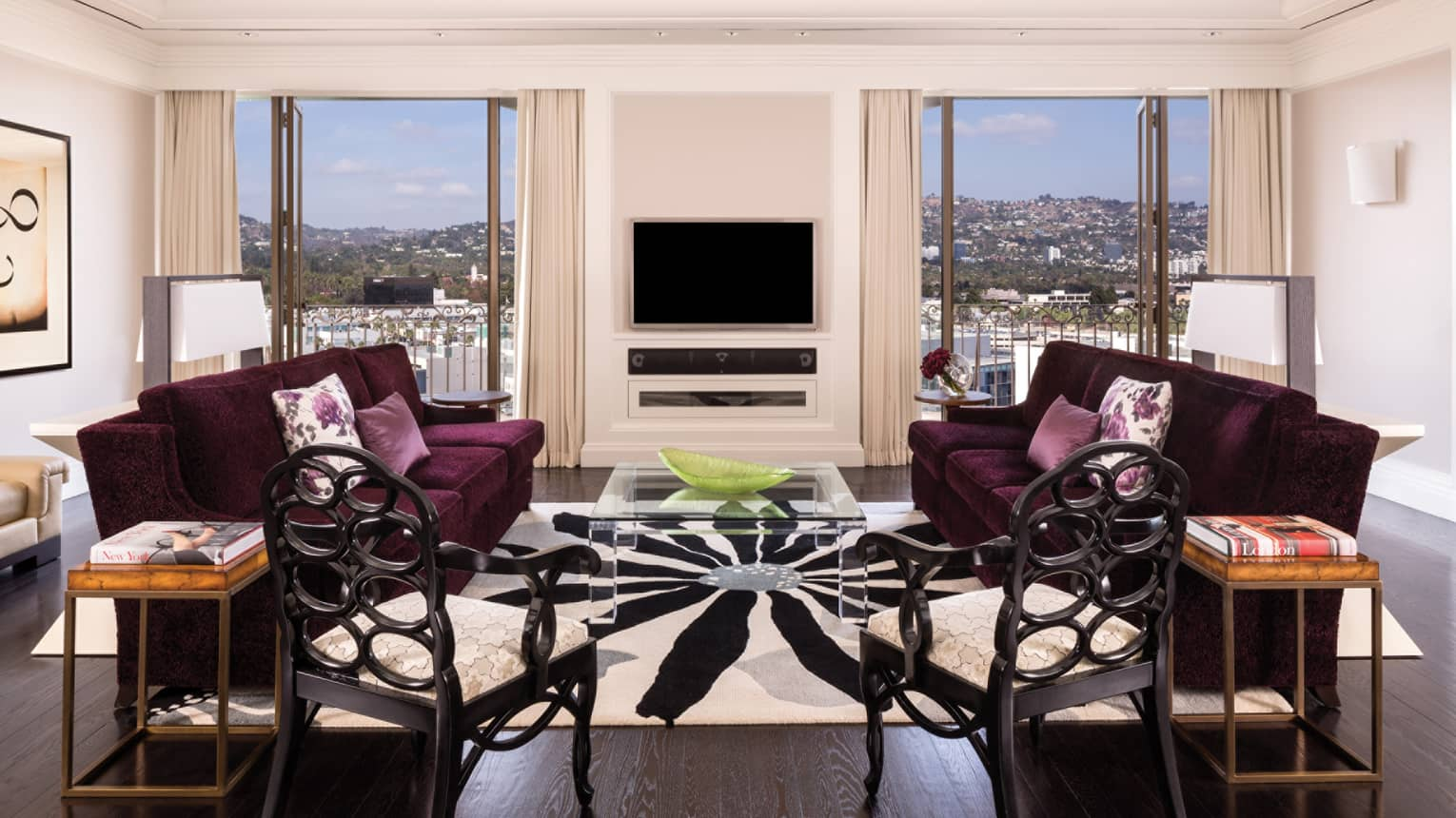Presidential Suite living room, chairs, purple loveseats by glass table, TV, two windows
