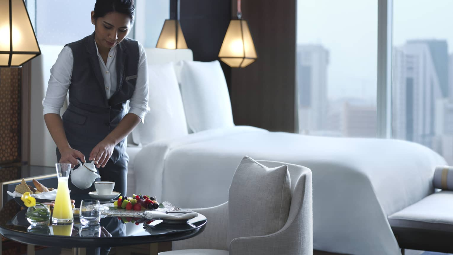 Woman in hotel suite pours tea into a white teacup next to a plate of fruit and bread.