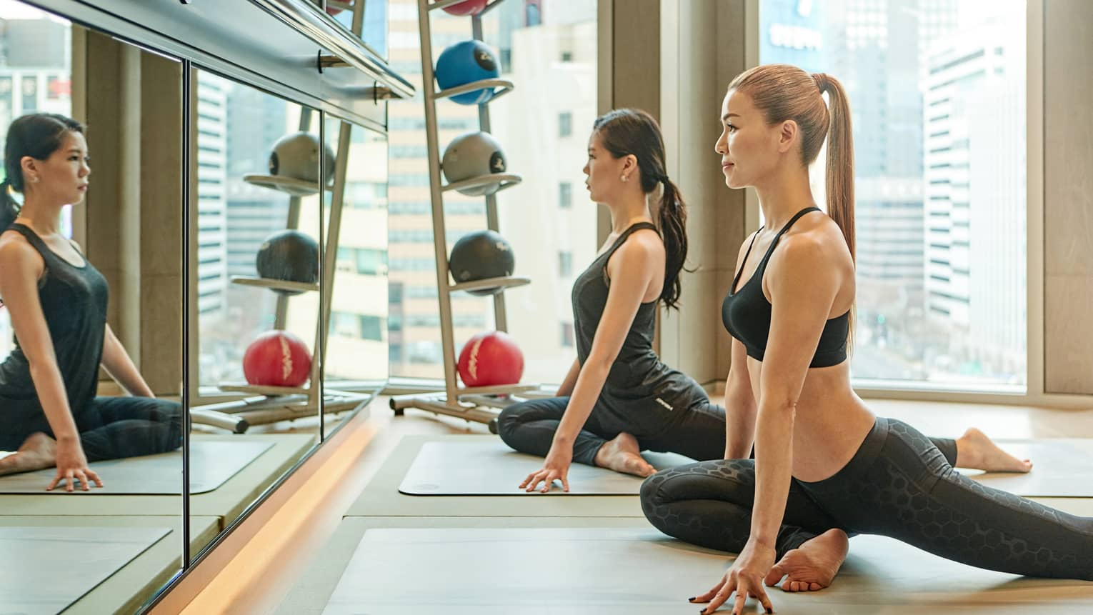 Two women sit on mats, stretch in yoga poses in front of wall mirror in Fitness Centre