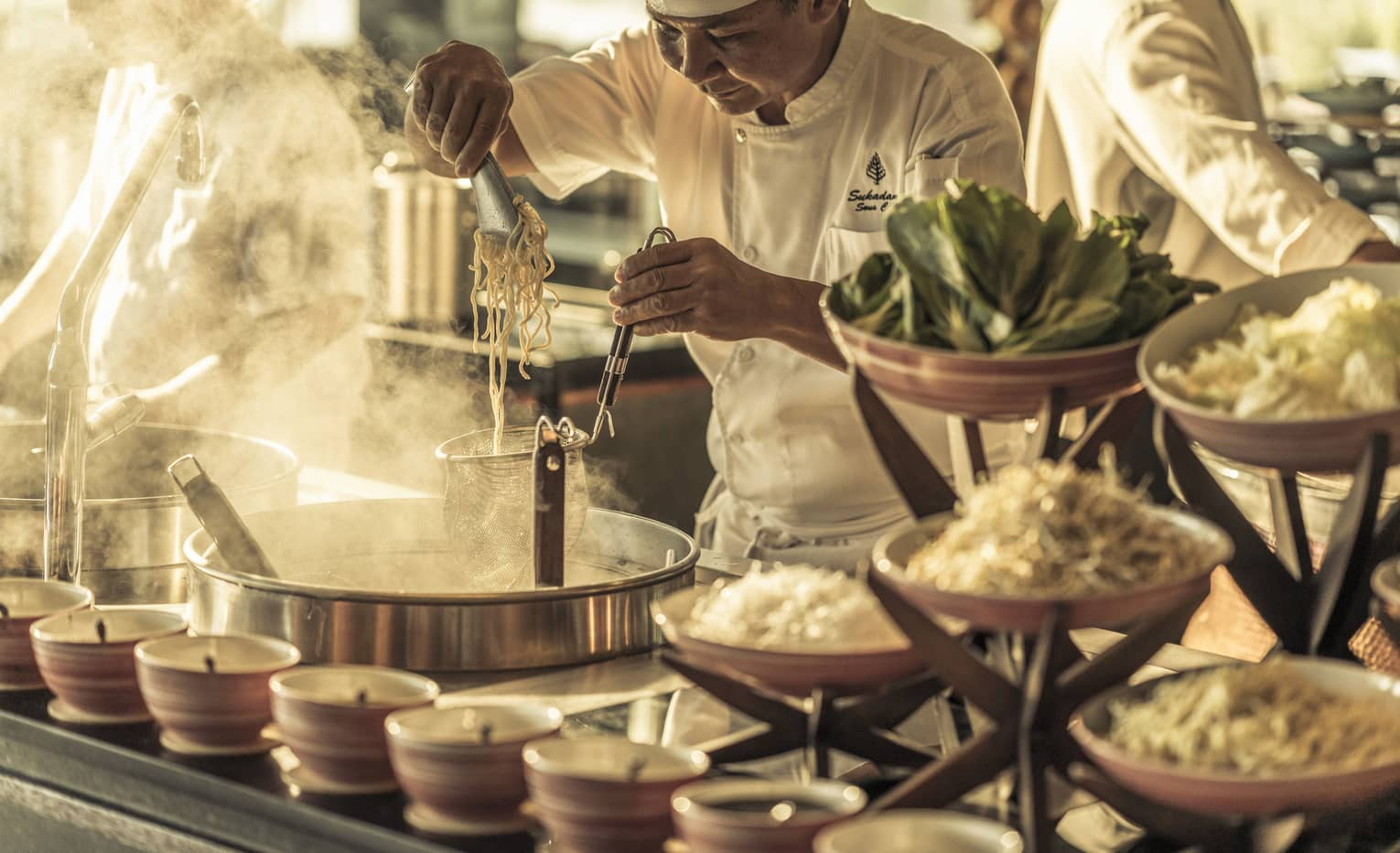 Chef cooking at a streetfood-style laksa and noodle station
