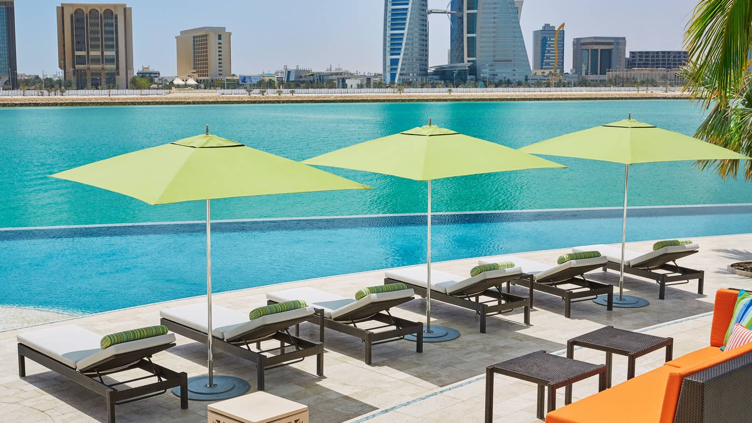 Six lounge chairs and three lime-green umbrellas in a row along infinity outdoor swimming pool