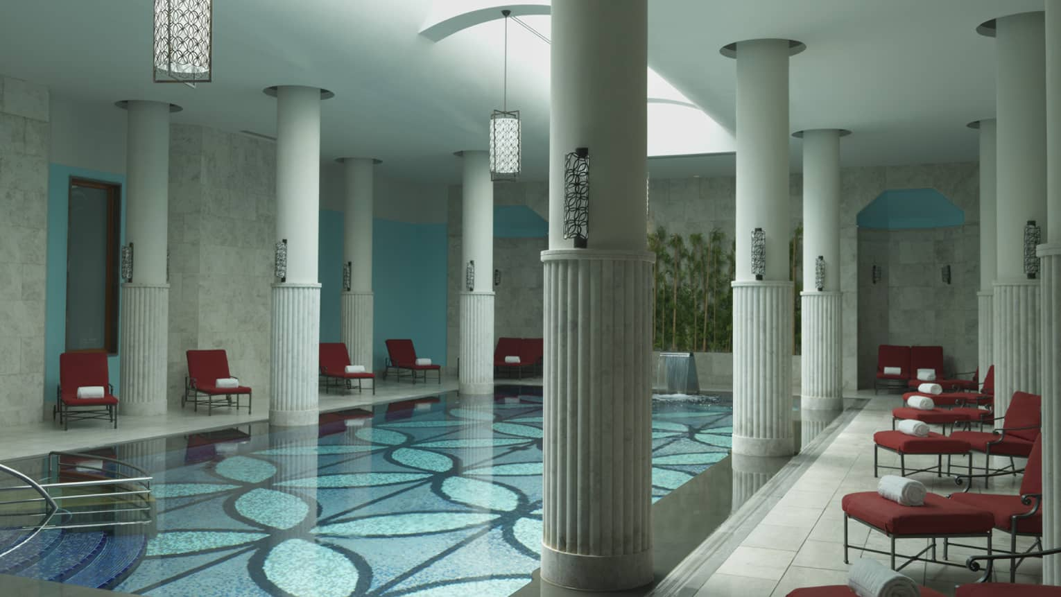 Tall white pillars around long indoor swimming pool