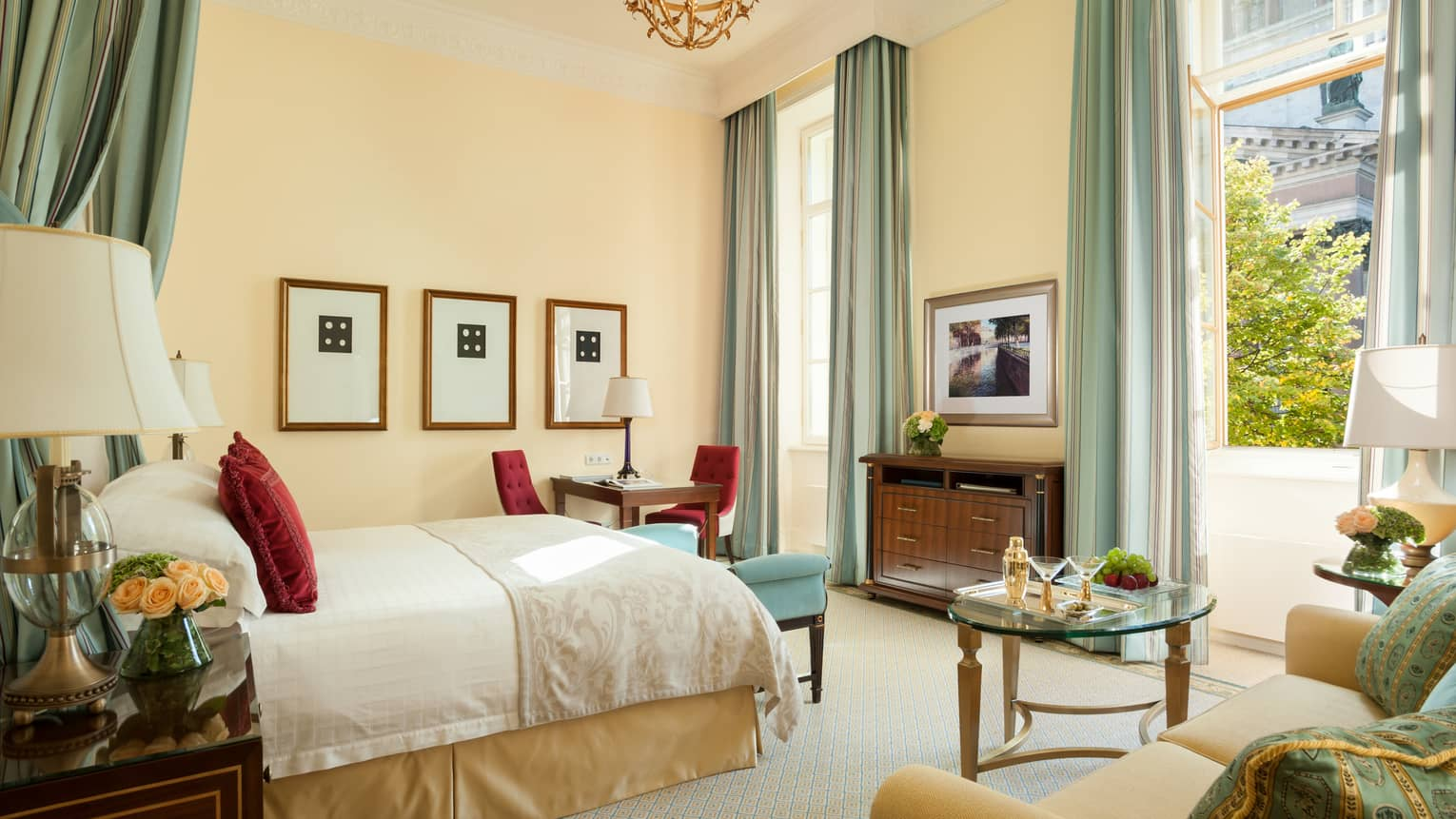 Four Seasons room with bed, loveseat, desk under high ceiling, pale blue and gold decor