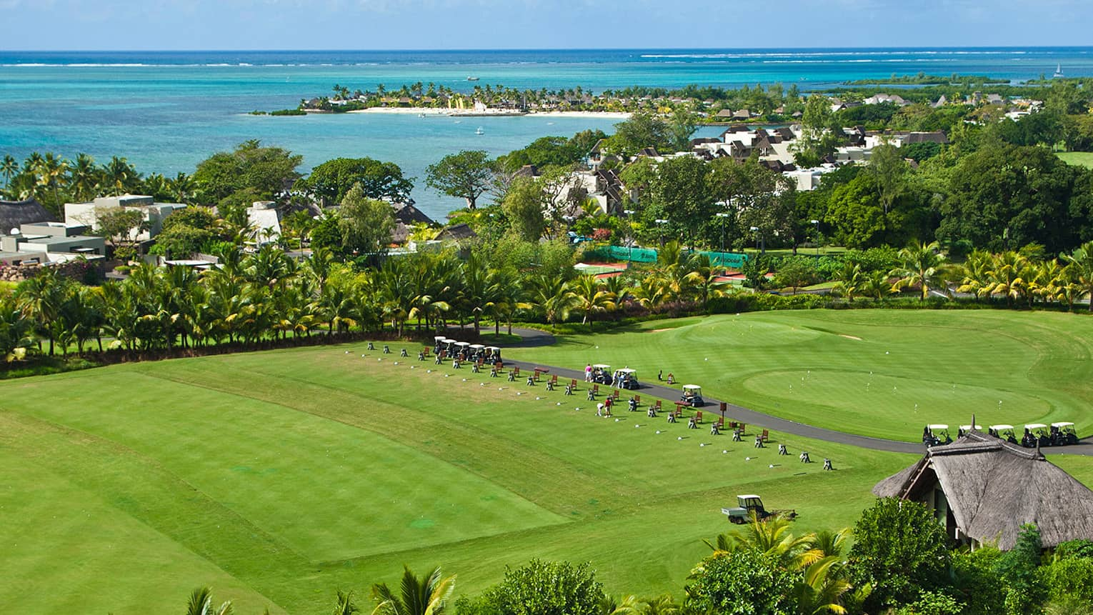 Looking down over large green lawn with rows of golf carts, trees and ocean
