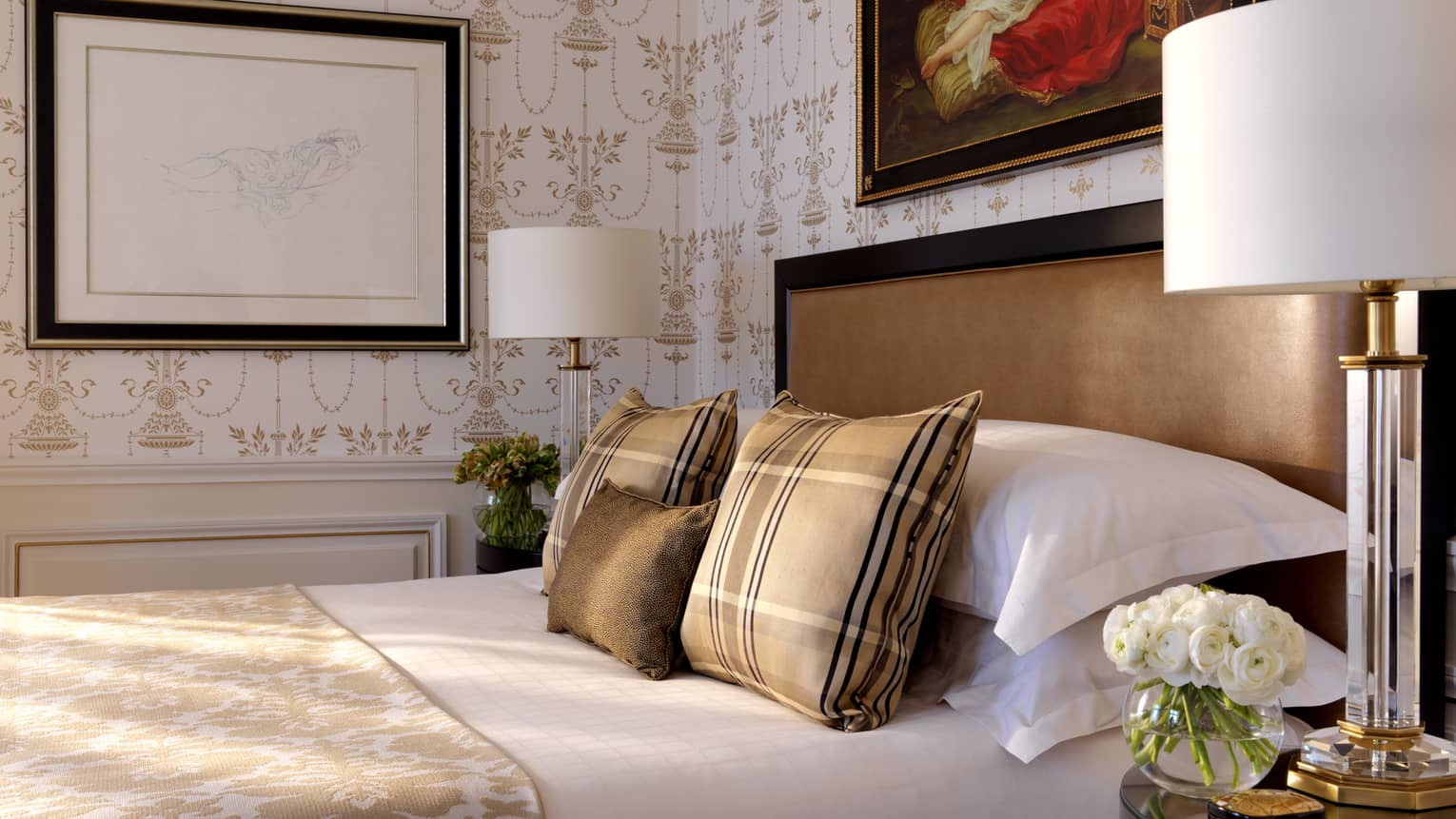 Close-up of bed with brown-and-gold plaid accent pillows, blanket, wallpaper, brown padded headboard