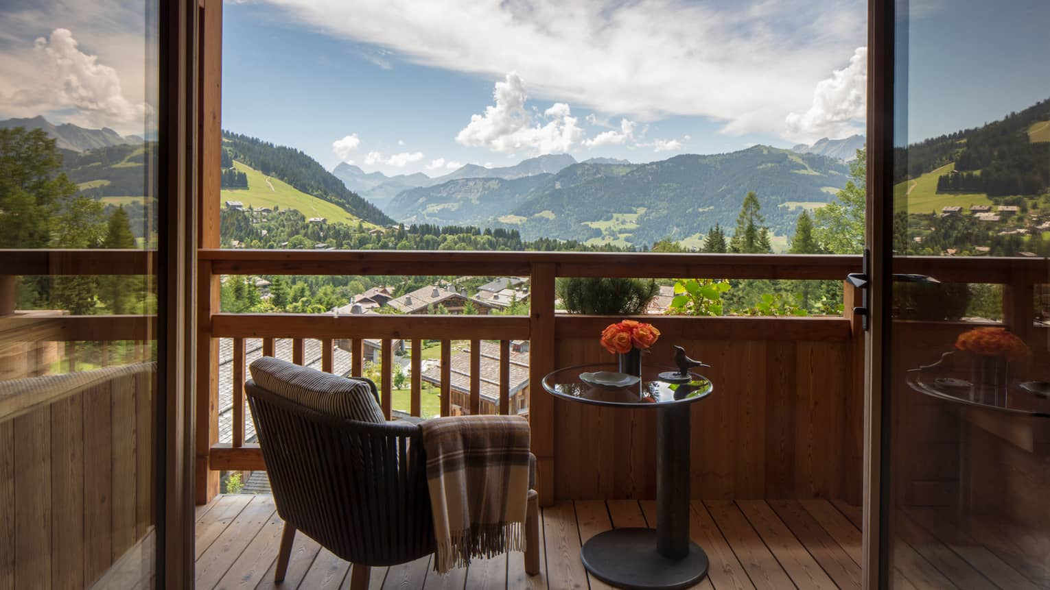 Suites des Alpes patio chair with blanket, table with flowers on balcony overlooking French Alps
