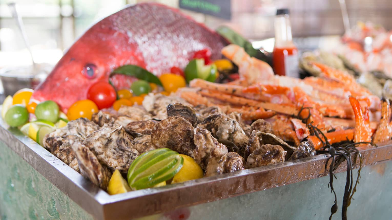 Large red fish on platter with clam shells, crab feet