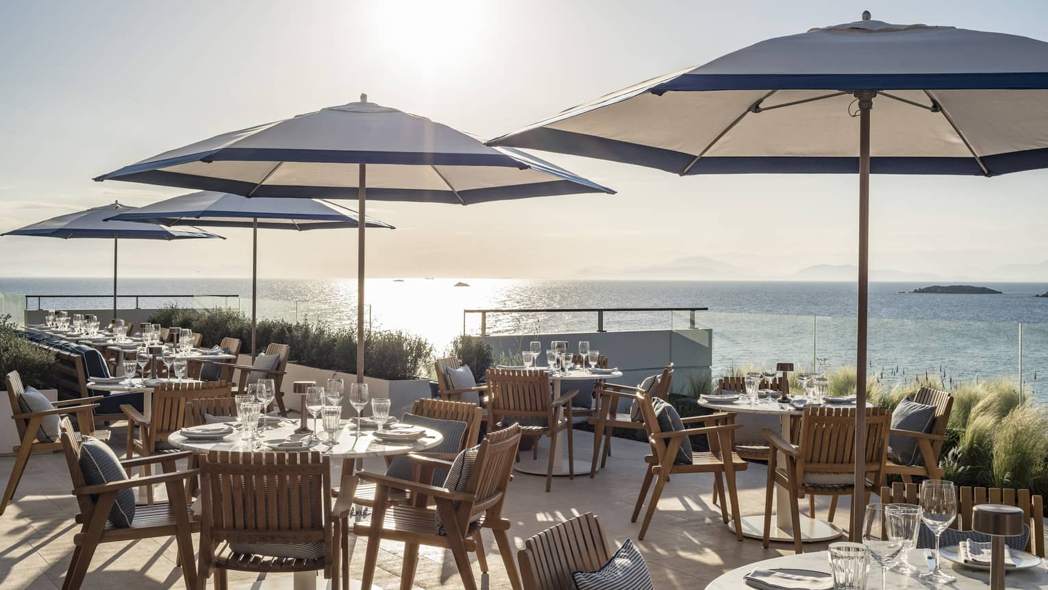 Sunny outdoor restaurant in Greece, blue umbrellas at wooden tables, overlooking the sea