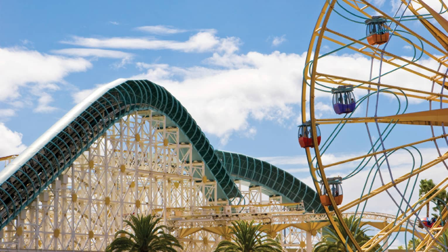 Side view of amusement park roller coaster track, ferris wheel over palm trees