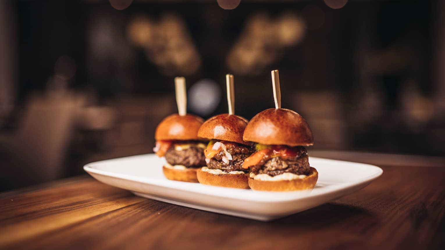 Trio of thick burgers on artisanal buns with wood sticks on white platter