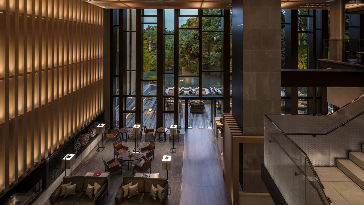 Looking down from soaring ceilings over Brasserie restaurant dining room, wood wall with lights