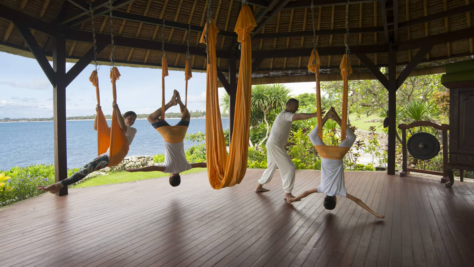 Guests hang from the ceiling as they are guided though rope yoga in an outdoor pavilion