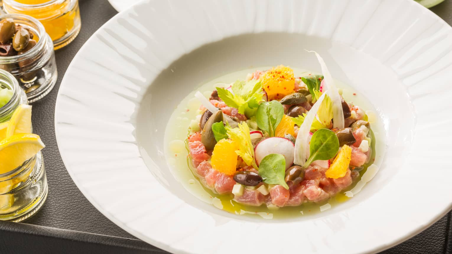 Tuna tartare salad with radish, orange slices in white bowl