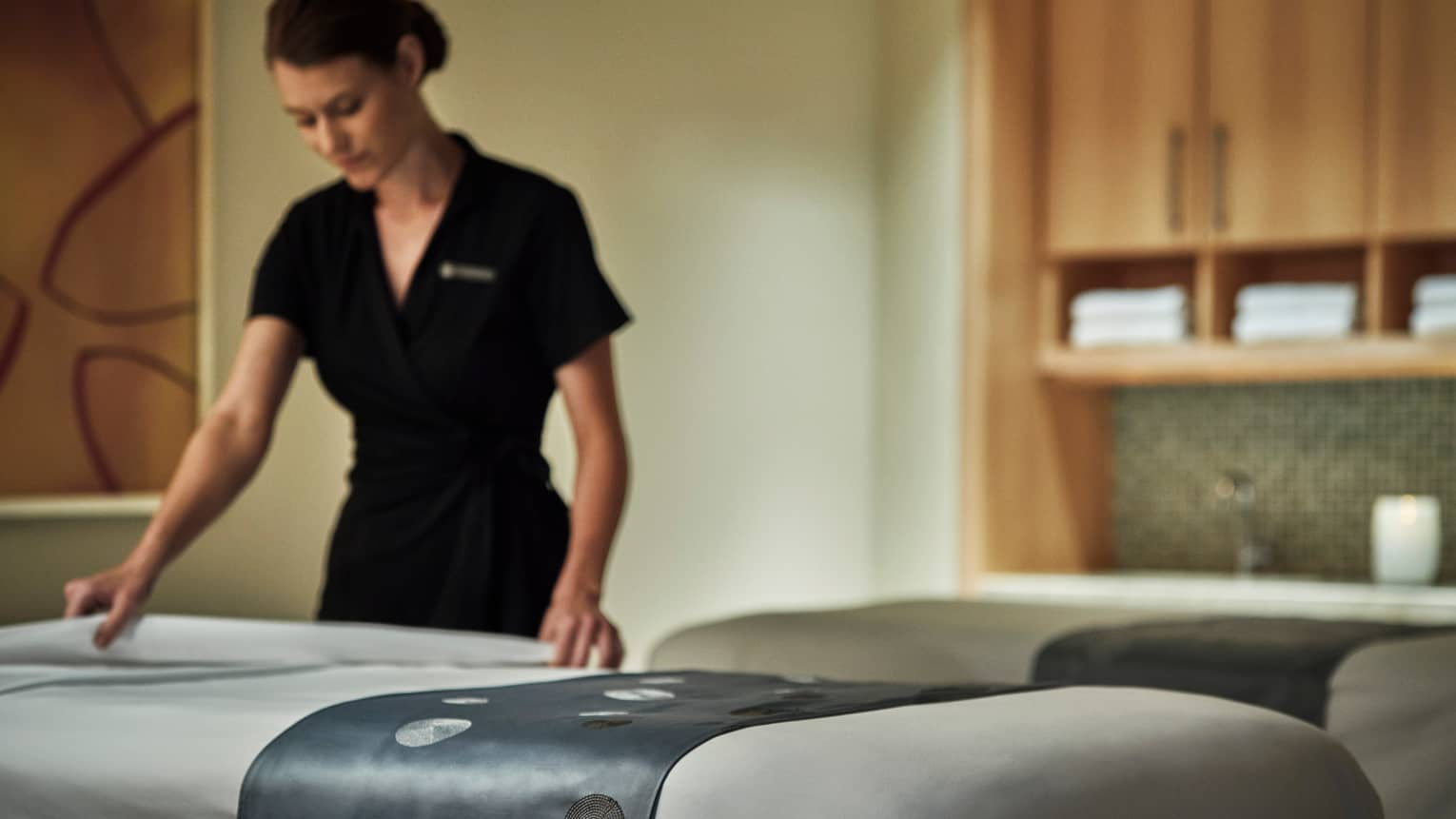 Spa attendant in black dress folds down white sheet on massage table