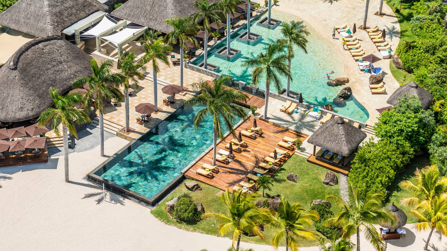 Aerial view of outdoor swimming pools, palm trees, patios on Four Seasons Mauritius resort