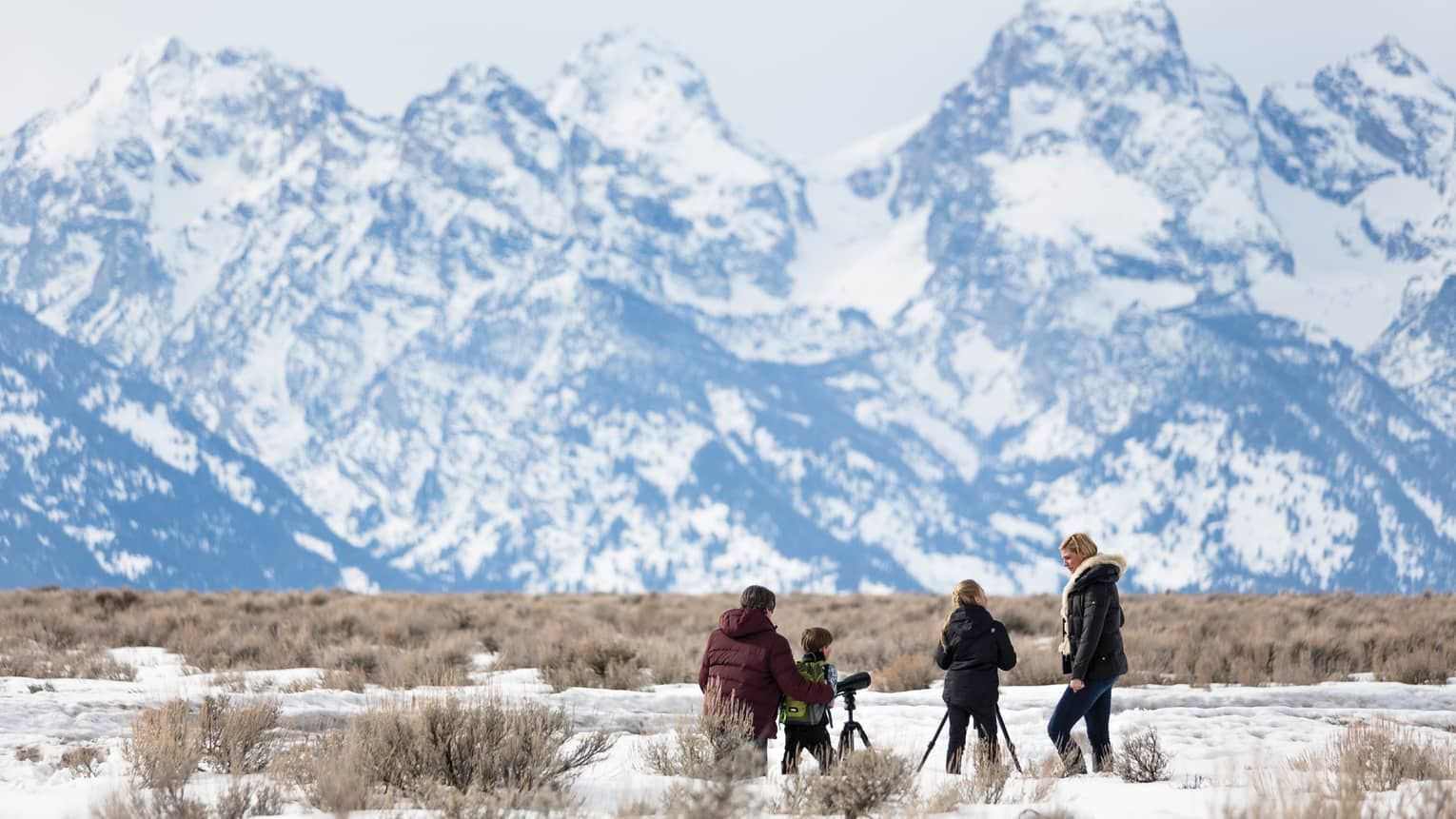 A family in winter apparel uses two telescopes to view a snowy mountain peaks
