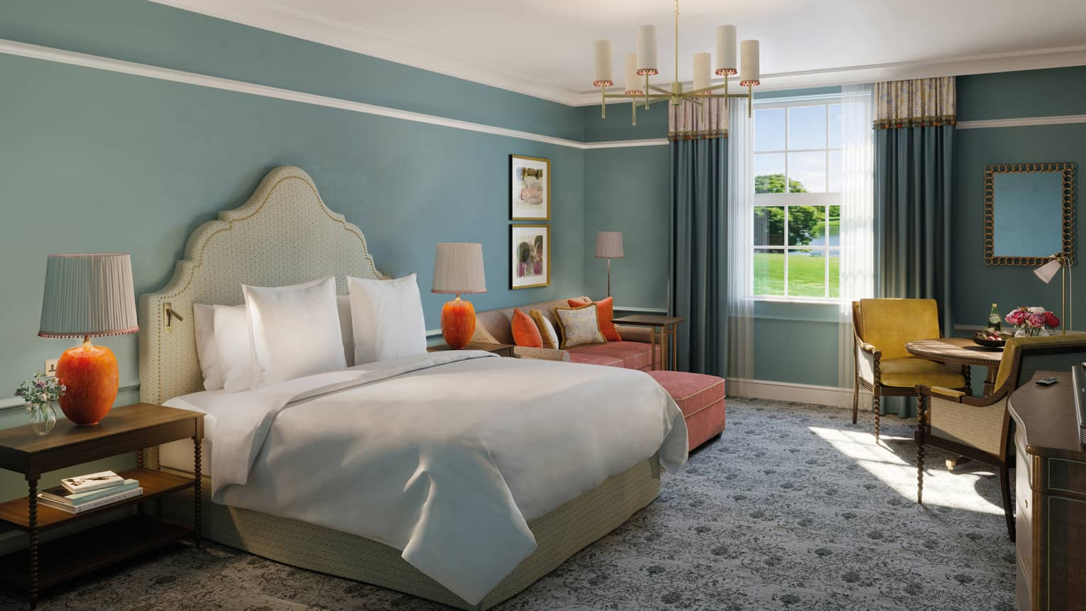 Guest room with beige fabric headboard and white linens, dusty blue walls, orange and yellow accent décor