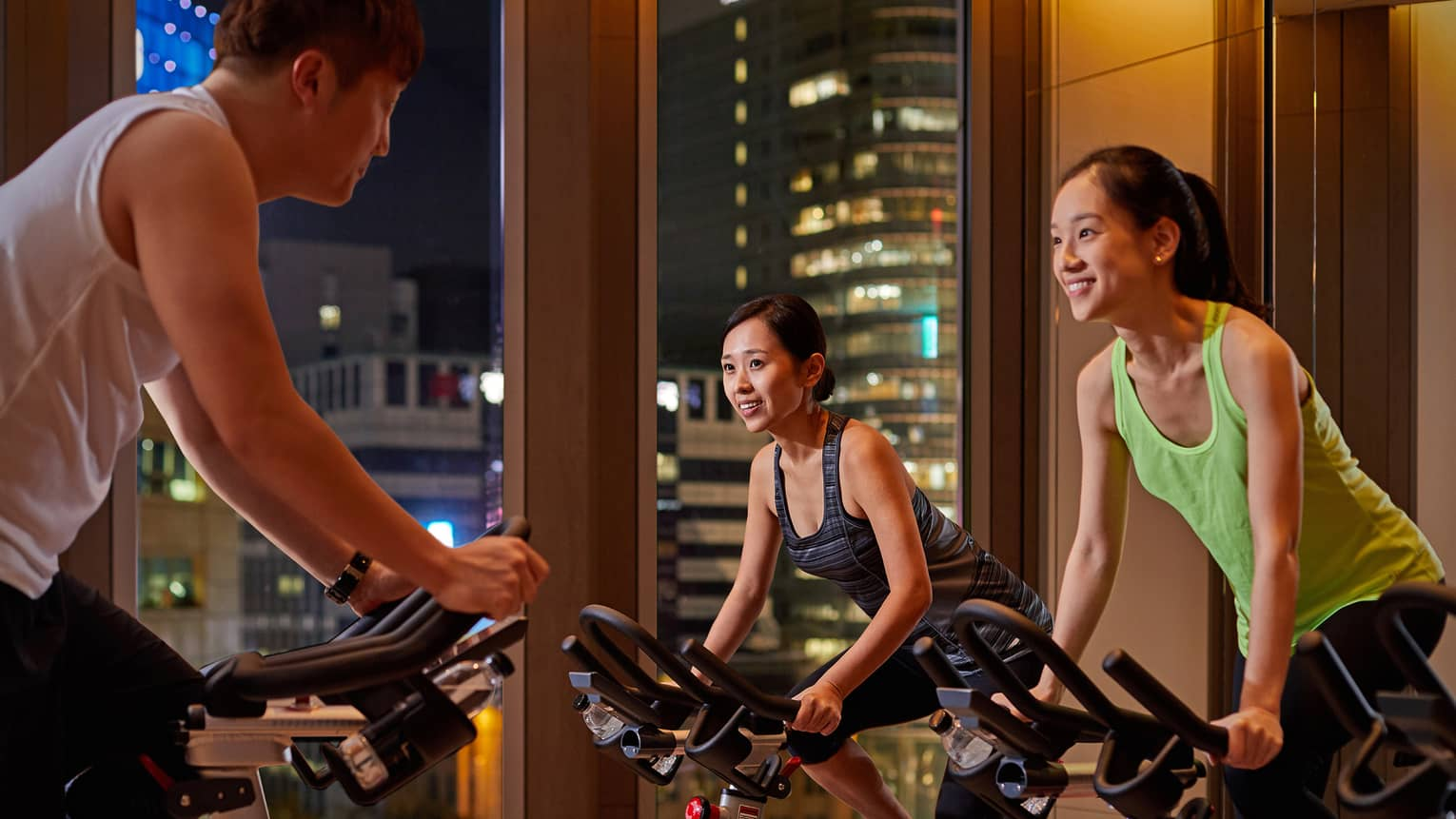 Man and two women on bikes in private spin class