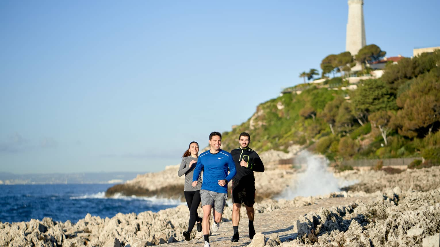 Three people jogging, smiling, on rocky trail beside the sea, lighthouse in backdrop