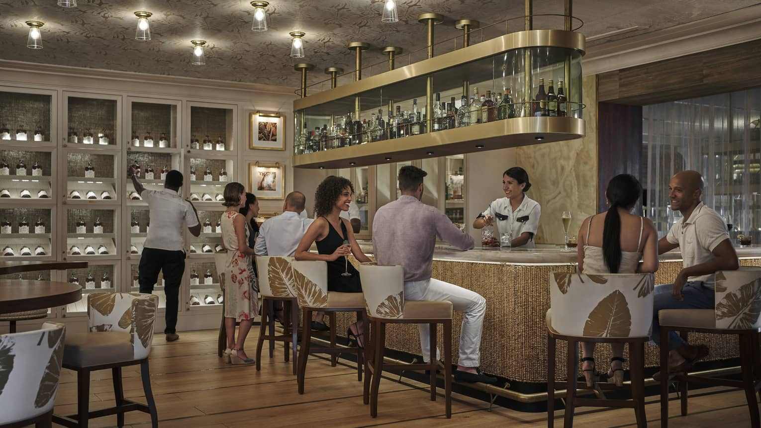 People mingle at a bar, with a hanging shelf holding bottles and a wall of wine shelving