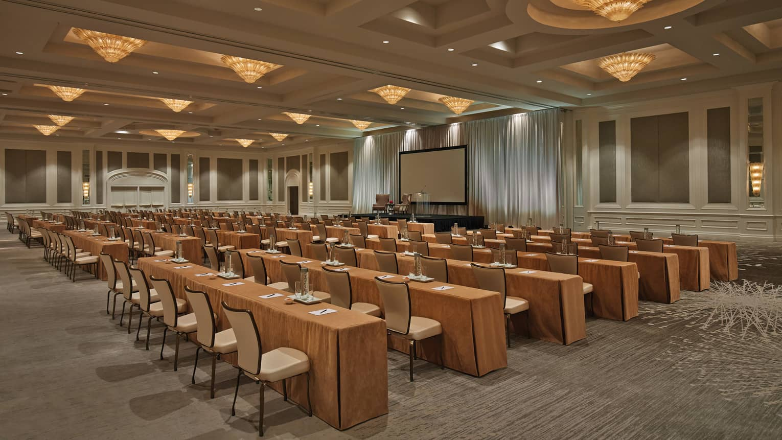 Conference with rows of meeting tables, chairs under cone-shaped lights in large ballroom