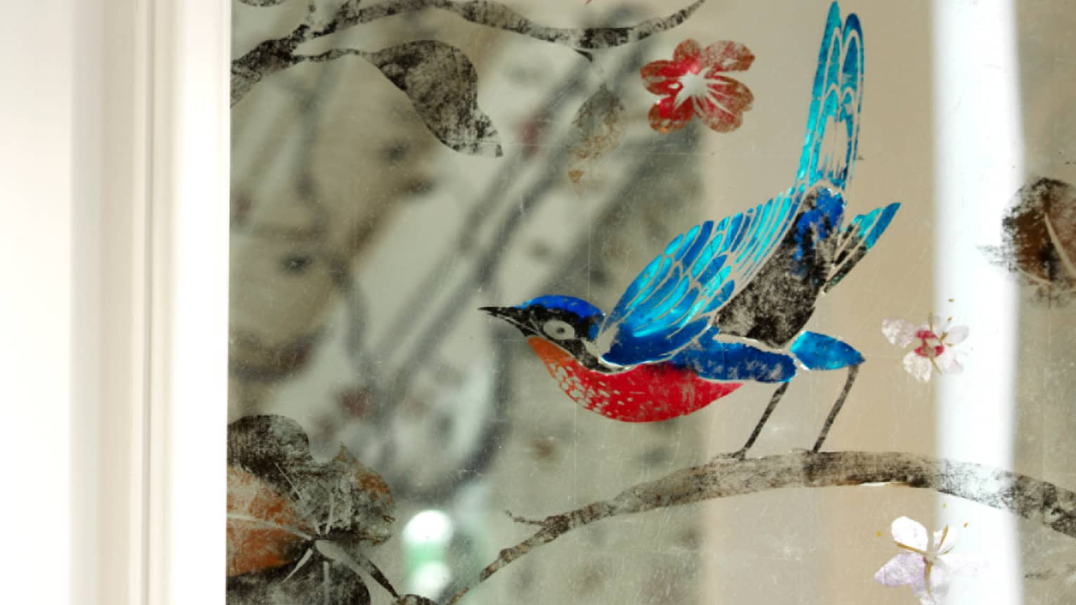 Coulourful painting of blue bird on branch, flowers on glass