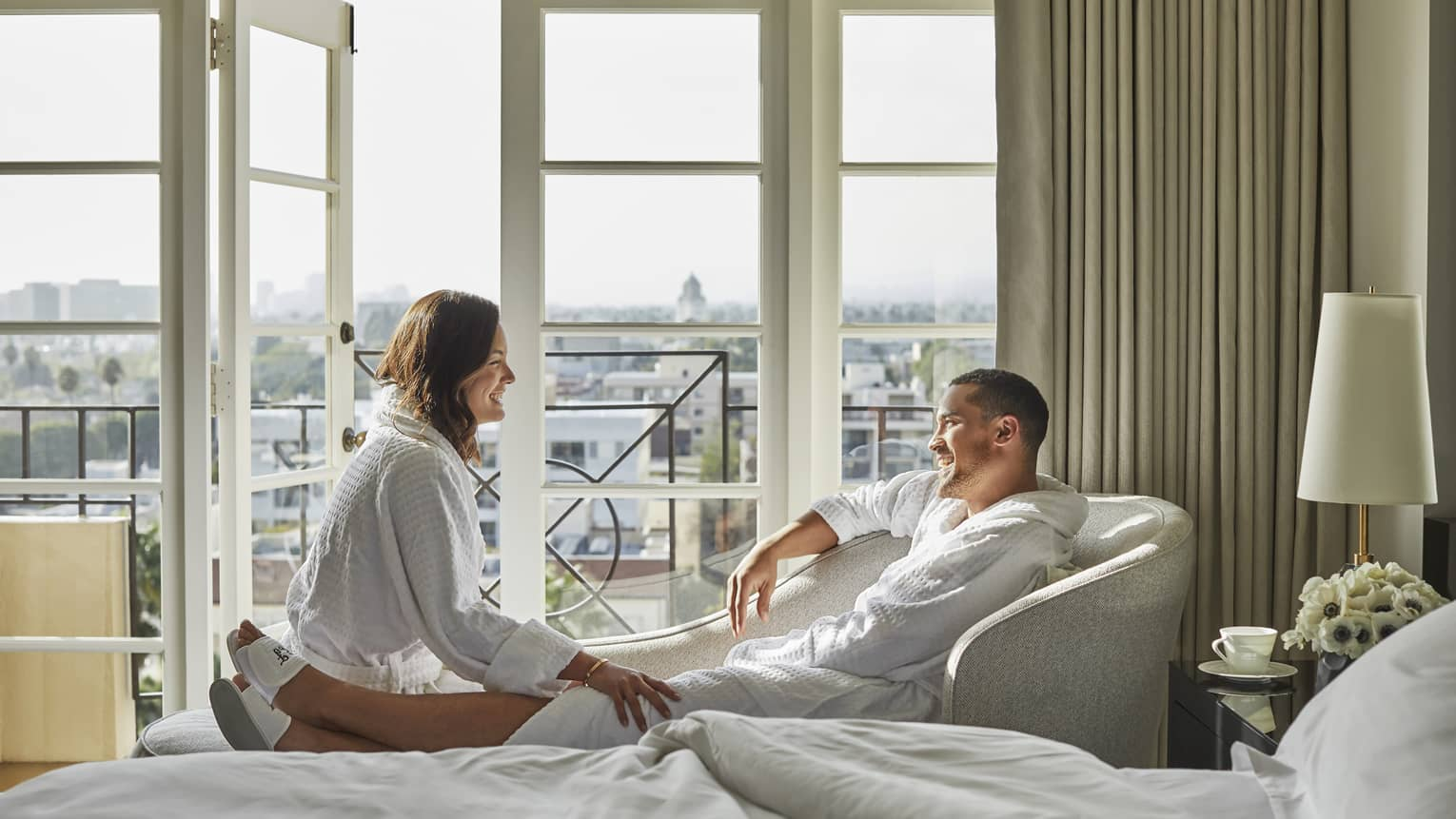 Smiling man and woman wearing bathrobes, lounging in front of sunny hotel room windows